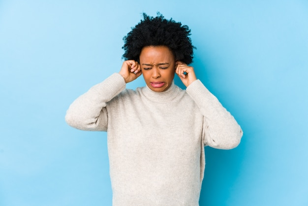 Женщина постаретая серединой афро-американская против голубой стены изолировала покрывать уши руками.