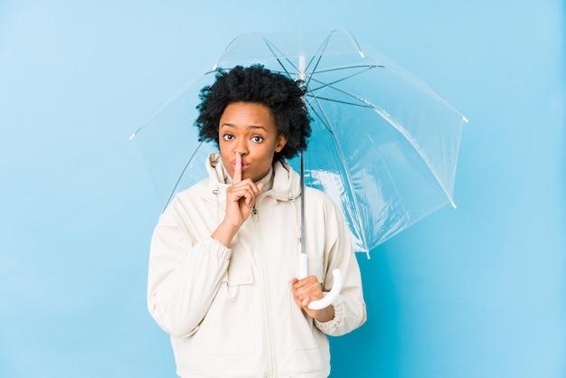 若いアフリカ系アメリカ人の女性は、秘密を守るか沈黙を求めて分離された傘を保持しています。