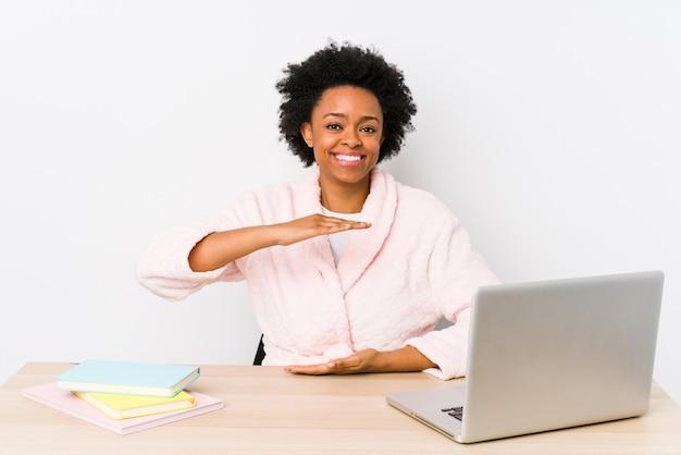 自宅で働く中年のアフリカ系アメリカ人女性は、製品のプレゼンテーション、両手で何かを保持分離しました。