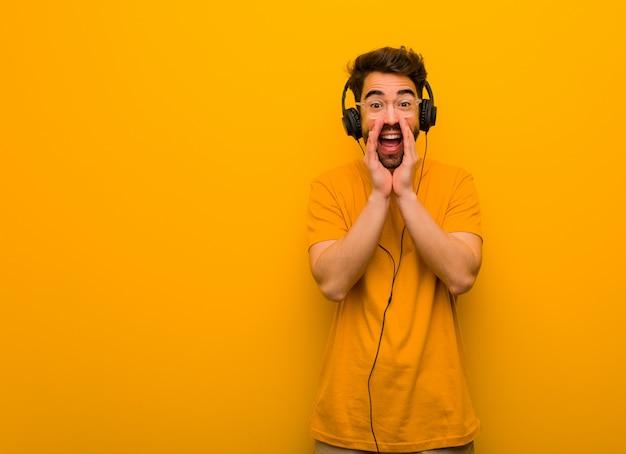 前方に幸せな何かを叫んで音楽を聴く若い男