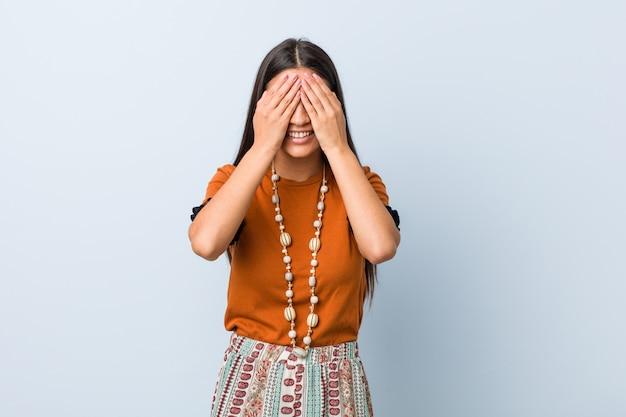 アラブの若い女性は目を手で覆い、笑顔は広く驚きを待っています。