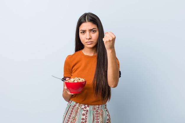 Молодая арабская женщина, держащая миску зерновых, показывая кулак с агрессивным выражением лица.