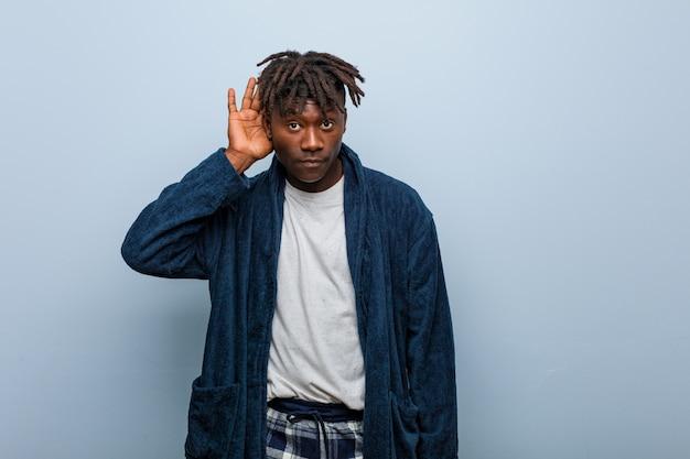 Пижама молодого африканского чернокожего человека нося пробуя слушать сплетню.