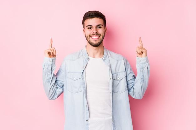 Молодой кавказский бизнесмен представляя в белой изолированной стене показывает с обоими пальцами передней части вверх показывая пустое пространство.