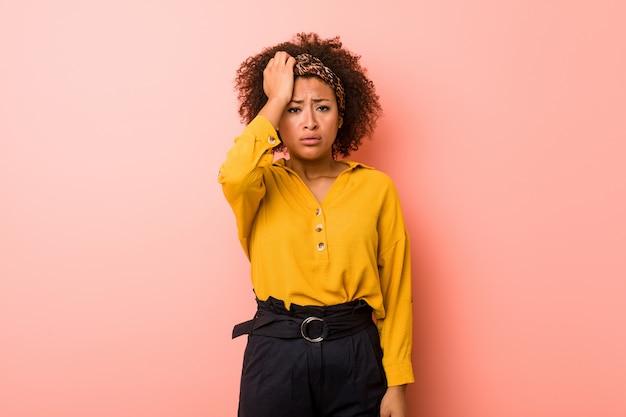Молодая афро-американская женщина против розовой стены утомляла и очень сонная держащ руку на голове.