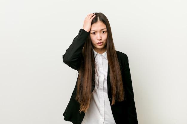 Молодая милая китайская бизнес-леди утомленная и очень сонная держа рука на голове.