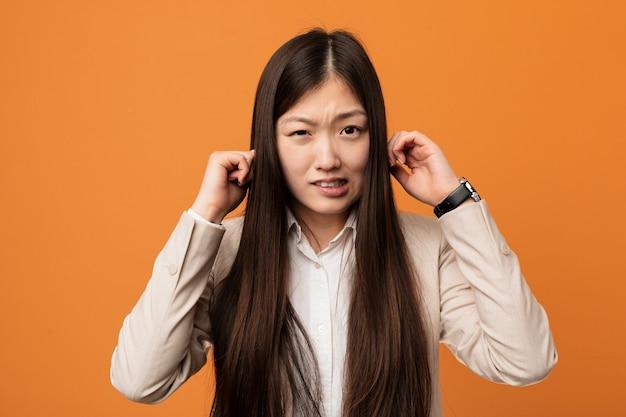 Молодой бизнес китайская женщина, охватывающих уши своими руками.