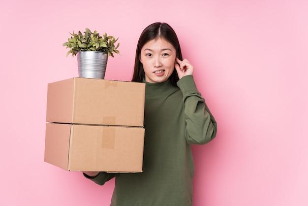 Молодая китайская женщина держа коробки изолировала покрывать уши руками.