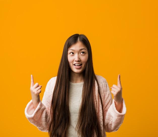 Молодая китайская женщина в пижаме показывает с обоими пальцами передней части вверх показывая пустое пространство.