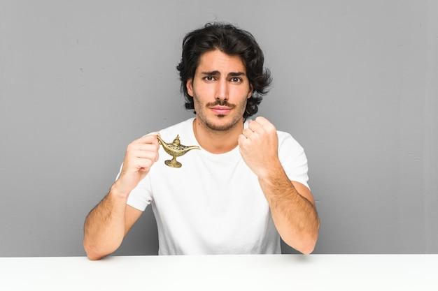 積極的な表情で拳を示す魔法のランプを保持している若い男。