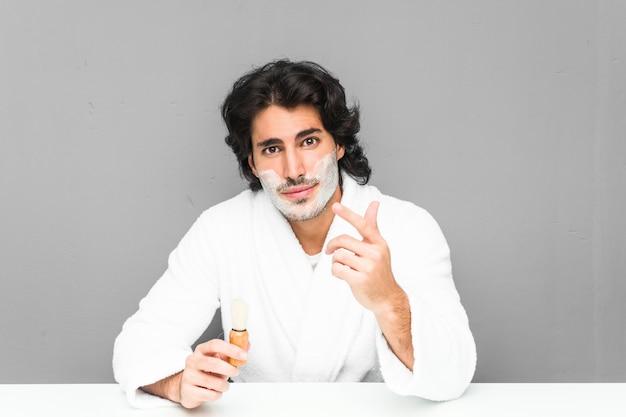 Молодой человек брить бороду, указывая пальцем на вас, как будто приглашая подойти ближе.