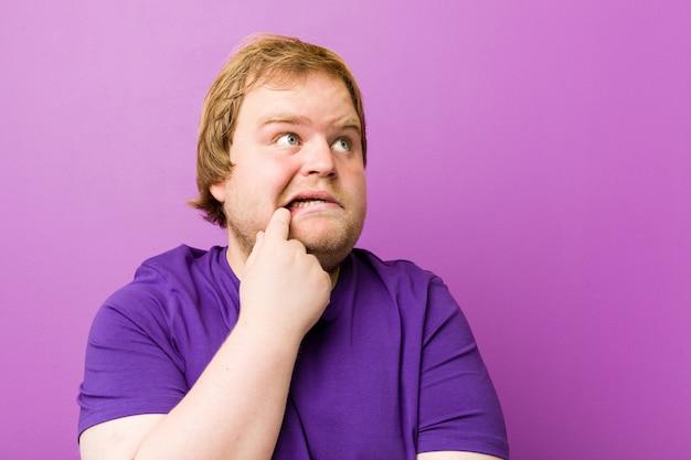若い本物の赤毛のデブ男は、コピースペースを見て何かについて考えてリラックスしました。