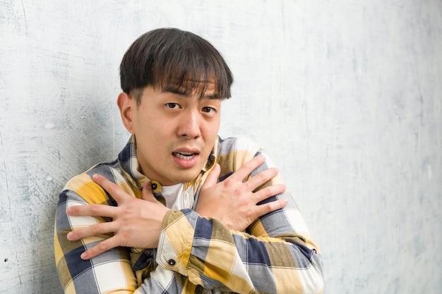 低温のため寒くなる若い中国人男性の顔のクローズアップ