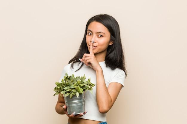 Молодая азиатская женщина держа завод держа секрет или прося безмолвие.