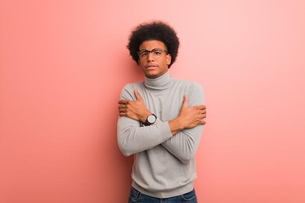 低温のため寒くなるピンクの壁の上の若いアフリカ系アメリカ人