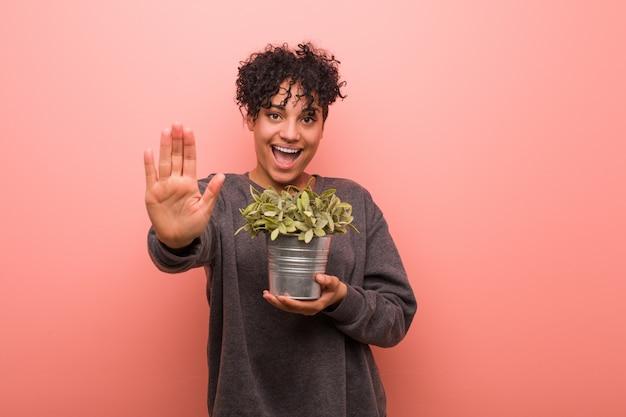 若いアフリカ系アメリカ人の女性が一時停止の標識を示す伸ばした手で立っている植物を保持して、あなたを防ぎます。