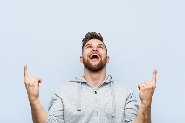 Молодой красивый человек фитнеса показывает с обоими пальцами передней части вверх показывая пустое пространство.