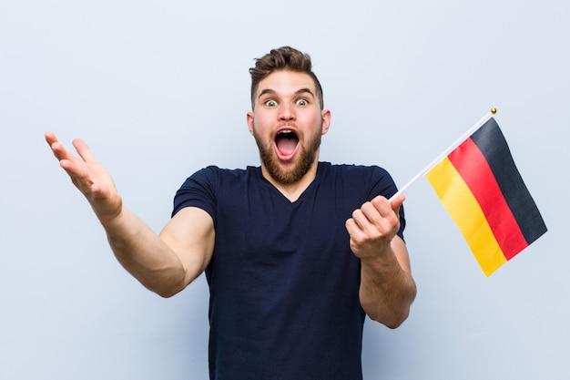 勝利または成功を祝っているドイツの旗を保持している若い白人男