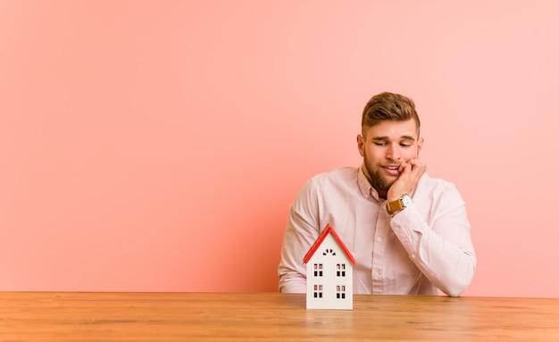 爪をかむ家のアイコンと座っている若い白人男、神経質で非常に不安。