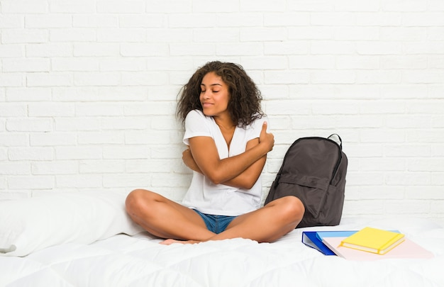 Молодой афроамериканец студент женщина на кровать обнимает, улыбаясь беззаботной и счастливой.