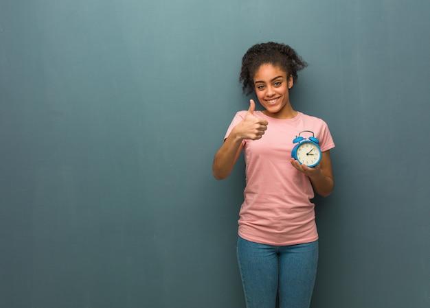 若い黒人女性の笑顔と親指を上げます。彼女は目覚まし時計を持っています。