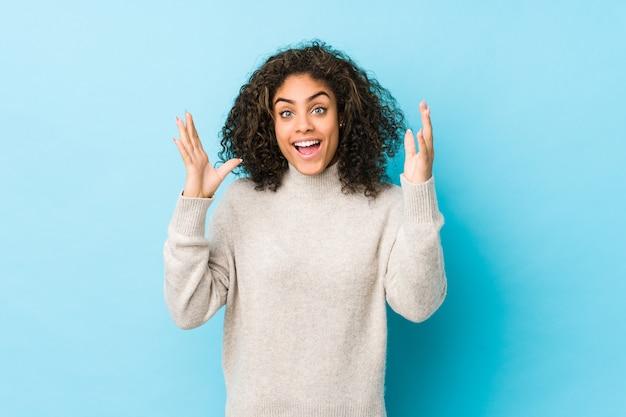 Молодые афро-американских вьющиеся волосы женщина получает приятный сюрприз, возбужденных и поднимать руки.