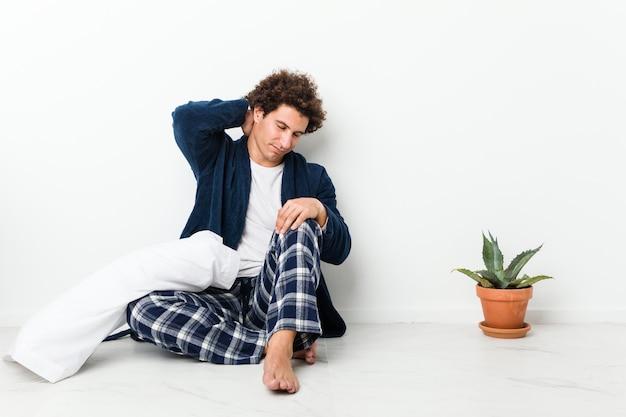 座りがちな生活のために首の痛みに苦しんでいる家の床に座ってパジャマを着ている中年の男性。