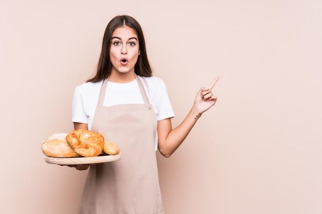 Молодая кавказская женщина пекаря изолировала указывать на сторону