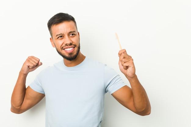 勝利、勝者の概念の後拳を上げる歯ブラシを保持している若い南アジアの男。