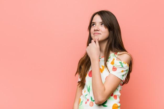 Девушка нося лето одевает против красной стены смотря косой с сомнительным и скептическим выражением.