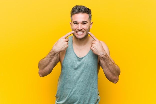 黄色の壁に対して若いフィットネス男笑顔、口で指を指しています。