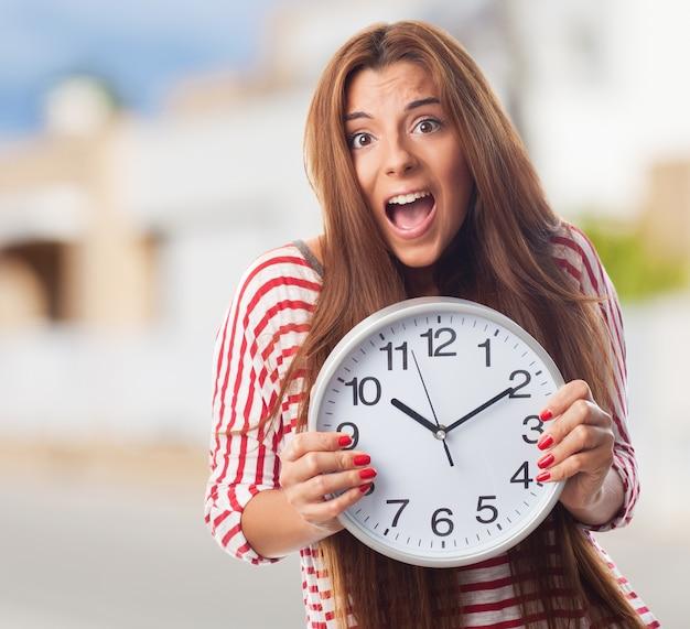 Молодая женщина прячется за круглые часы на стене.