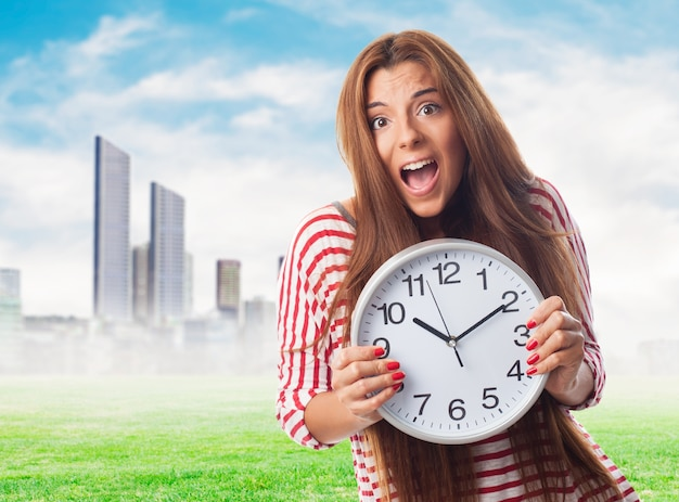 大きな時計とハリーでグラマラスな女の子。