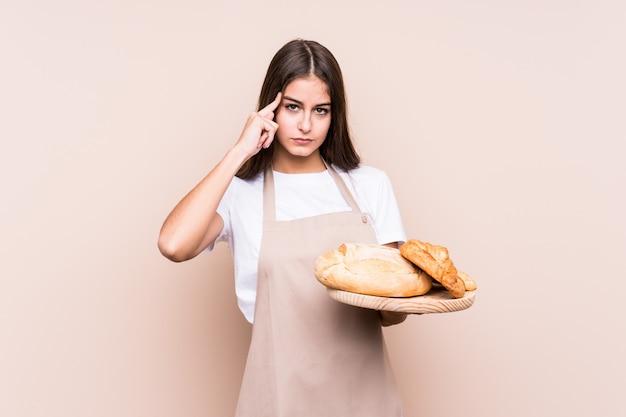 Молодой кавказской пекарь женщина изолированных указывая храм с пальцем, думая, сосредоточены на задачу.