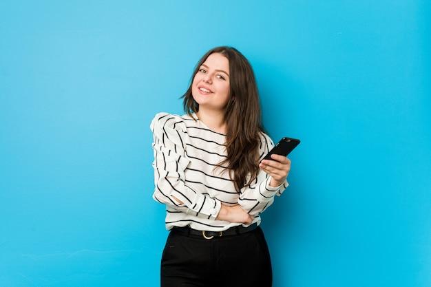 笑って、楽しんで電話を保持している若い曲線の女性。