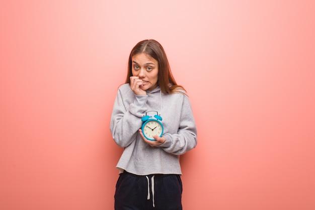 Молодая красивая кавказская женщина, кусающая ногти, нервная и очень взволнованная. она держит будильник.