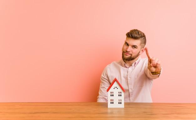 指でナンバーワンを示す家のアイコンと座っている若い白人男。