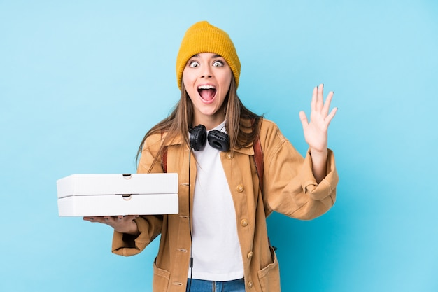 ピザを保持している若い白人女性は、楽しい驚きを受け取って、興奮して手を上げて分離しました。