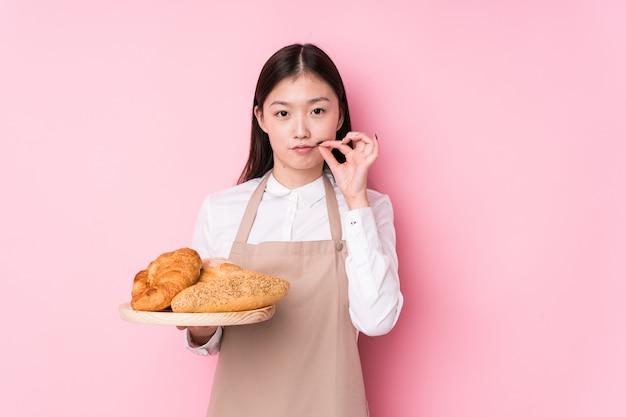 Молодая китайская женщина хлебопека изолированная с пальцами на губах держа секрет.