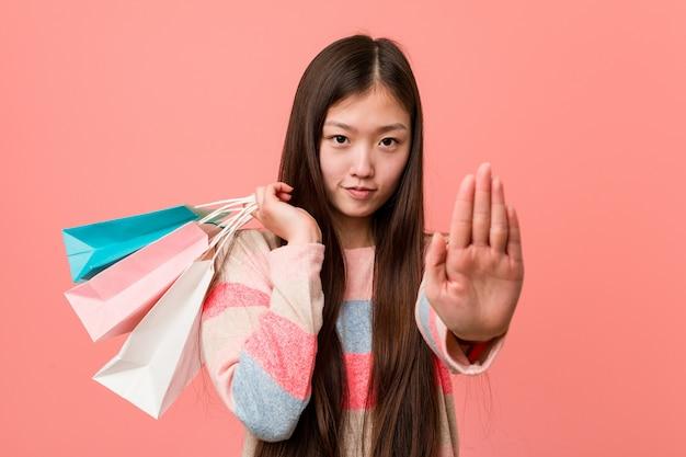 Молодая азиатская женщина держа хозяйственную сумку стоя при протягиванный знак стопа показа руки, предотвращая вас.