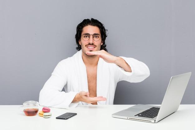 Молодой красивый человек работая после ливня держа что-то с обеими руками, представление продукта.