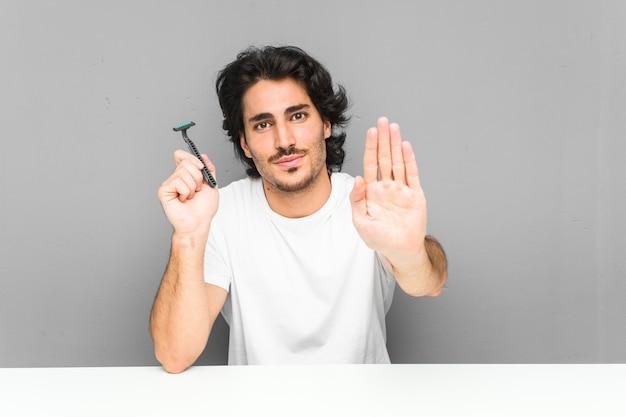 一時停止の標識を示す伸ばした手で立っているかみそりの刃を保持している若い男は、あなたを防ぎます。