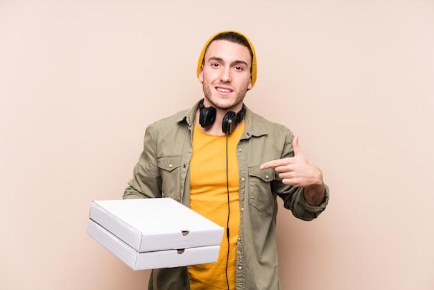 Молодой кавказский человек держа персону пицц указывая вручную к космосу экземпляра рубашки, гордый и уверенно