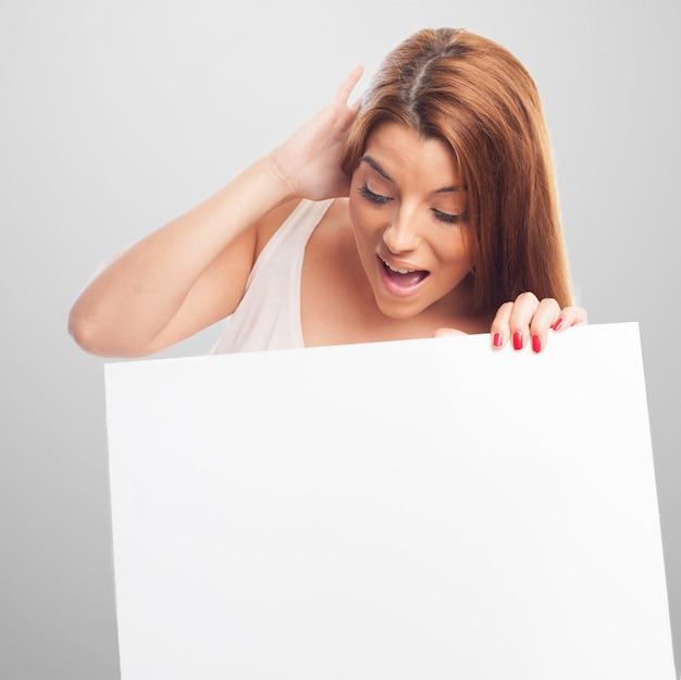 Поражен женщина, глядя на рекламный щит