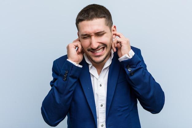 Молодой бизнес кавказских человек, охватывающих уши своими руками.