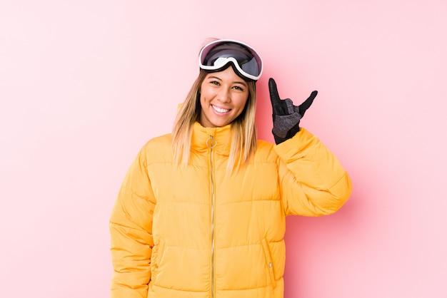 Молодая кавказская женщина нося лыжи одевает в розовой стене показывая жест рожков как концепция революции.