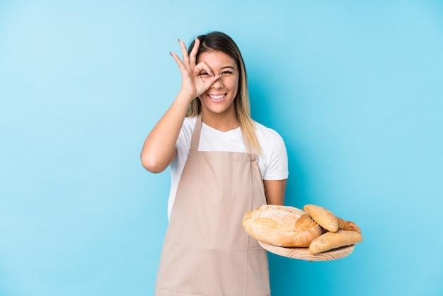 Молодая кавказская женщина хлебопека изолировала взволнованный держать одобренный жест на глазе.