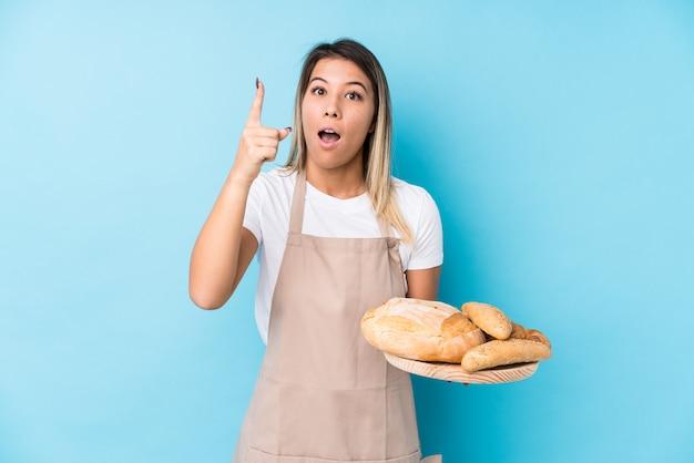 Молодая кавказская женщина хлебопека изолировала иметь идею, концепцию воодушевленности.