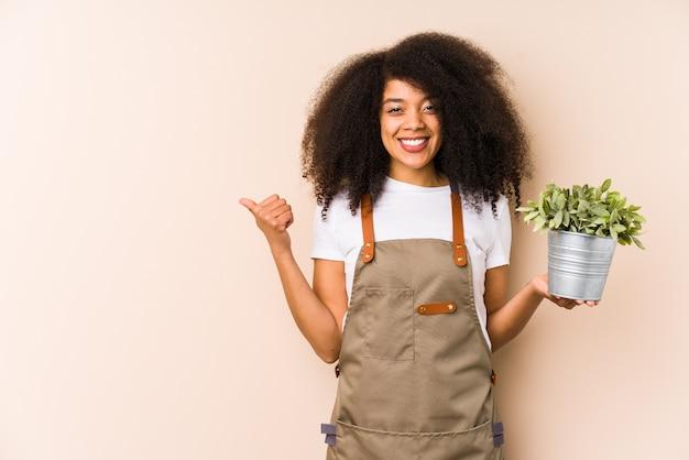 分離された植物を保持している若いアフロ庭師女性笑顔と親指を上げる