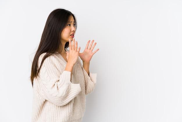 Молодая китаянка изолированные кричит громко, держит глаза открытыми и руки напряженными.